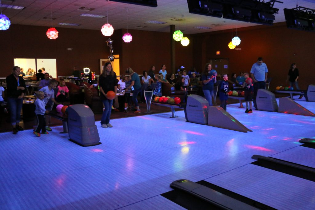 Company event at a bowling alley showing a large group of people bowling