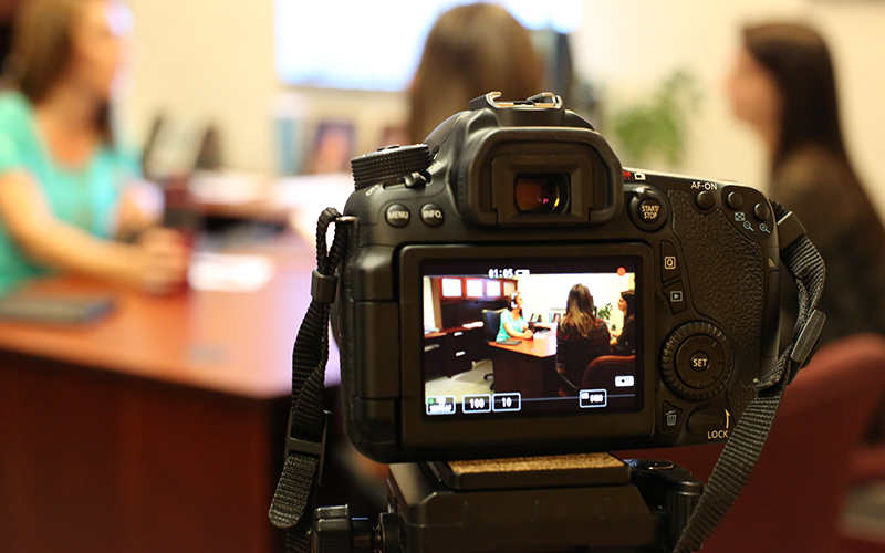 Camera videotaping women at a desk